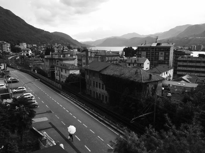 Rain Drops Mountain Italy Travel Travel Photography Umbrella Lonely Rain Melancholy Meaningoflife Lake Walking Around Streetphotography Blackandwhite Photography Blackandwhitephotography Architecture Built Structure Building Exterior High Angle View Transportation Sky Road Day Outdoors Mountain Range City No People Nature EyeEmNewHere