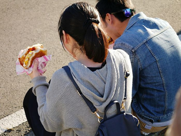 Rear view of man and woman eating burger while sitting outdoors