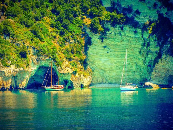 The KIOMI Collection Cliff Cliffs Rock Rocks Boat Sailboat Rocks And Sea Sailboats Boats Sea Seascape Cliff And Sea Paxi Island Greek Islands Share Your Adventure Shades Of Blue Crystal Clear Waters Cave Cave Entrance Beach Beach Photography Landscapes Transportation