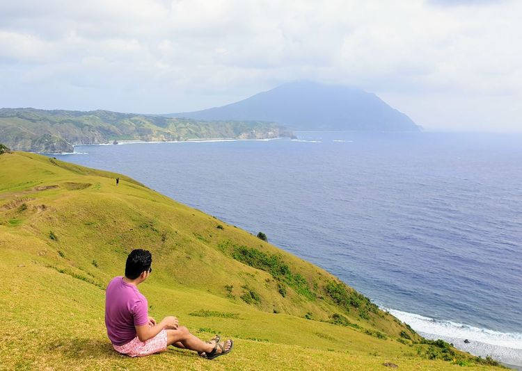 Full length of man looking at seascape while sitting on mountain
