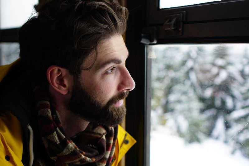 Close-up of man looking at window during winter