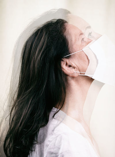 Multiple exposure image of woman wearing mask looking away against white background