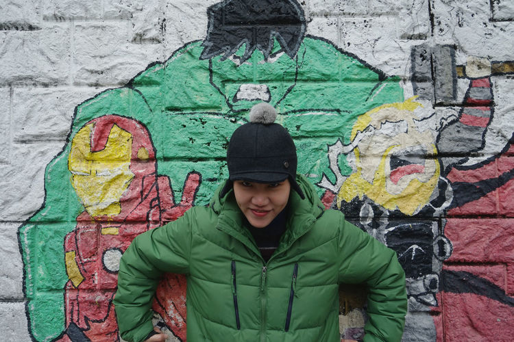 Graffiti Green Inner Power Adolescence  Architecture Art And Craft Built Structure Creativity Day Front View Graffiti Green Color Hood - Clothing Hulk Leisure Activity Lifestyles Looking At Camera One Person Outdoors Portrait Real People Standing Teenager Wall Wall - Building Feature Warm Clothing Young Adult