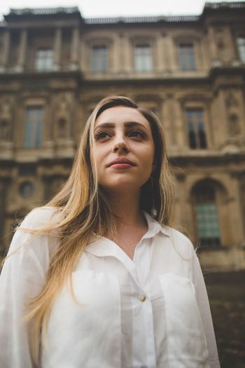 Portrait of beautiful woman standing against building