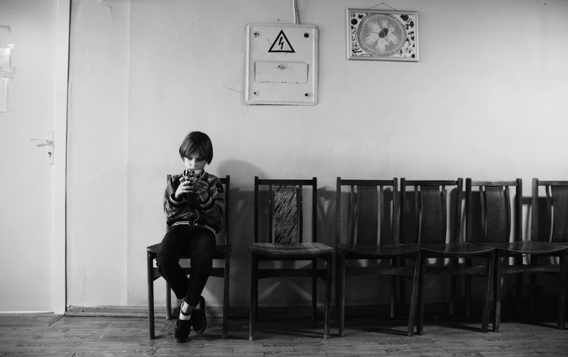 Rear view of kid sitting on chair in a corridor