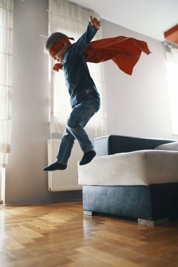 Full length of boy jumping on sofa at home