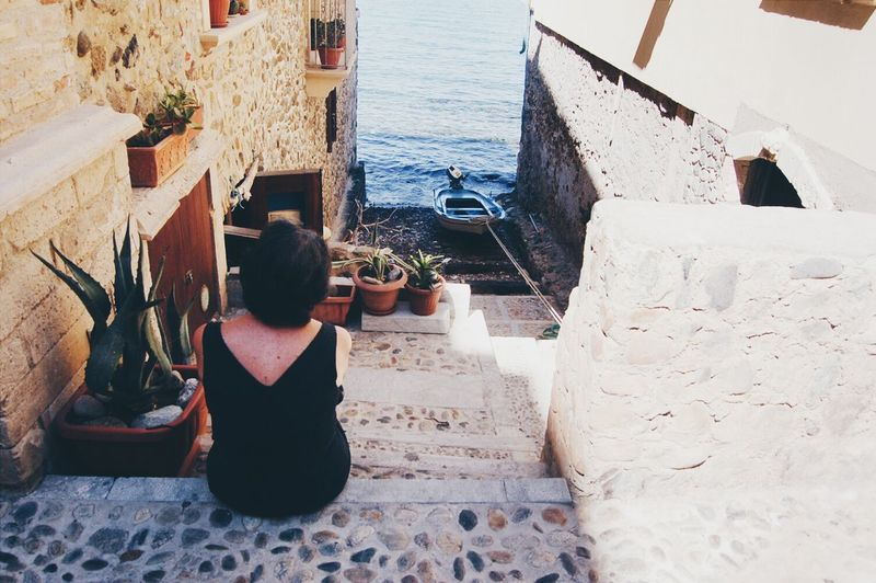 Rear view of woman sitting on steps against sea