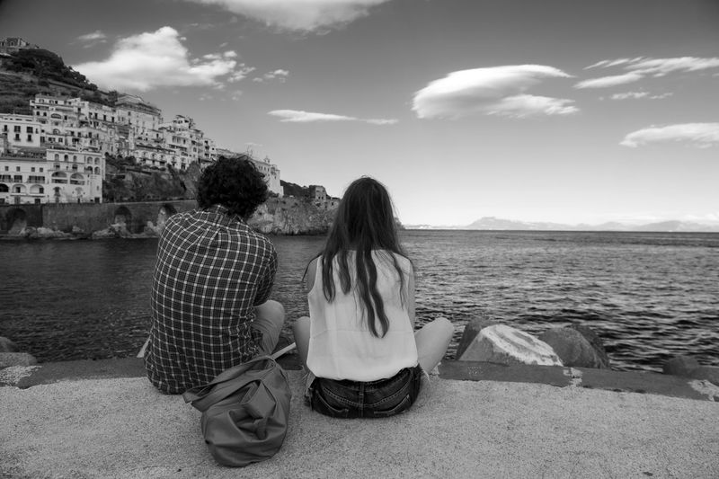 Rear view of man and woman sitting by sea against sky in town