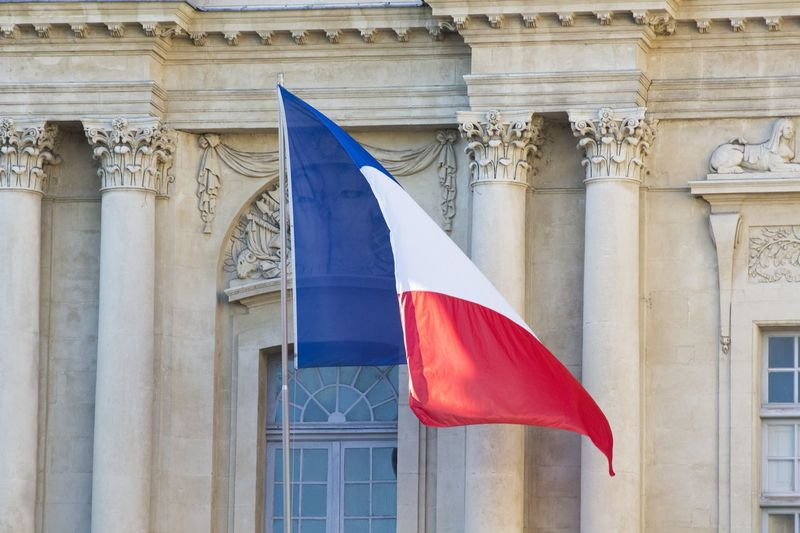 Low angle view of france flag against built structure