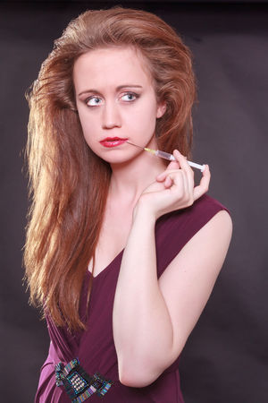 Female Model Holding Injection to Lips on black background. Botox Injektion Aesthetic Aging Beauty Dyed Hair Facial Fashion Fashion Model Leisure Activity Lifestyles Lipstick Long Hair Looking At Camera Make-up One Person Portrait Real People Red Redhead Standing Syringe Women Young Adult Young Women
