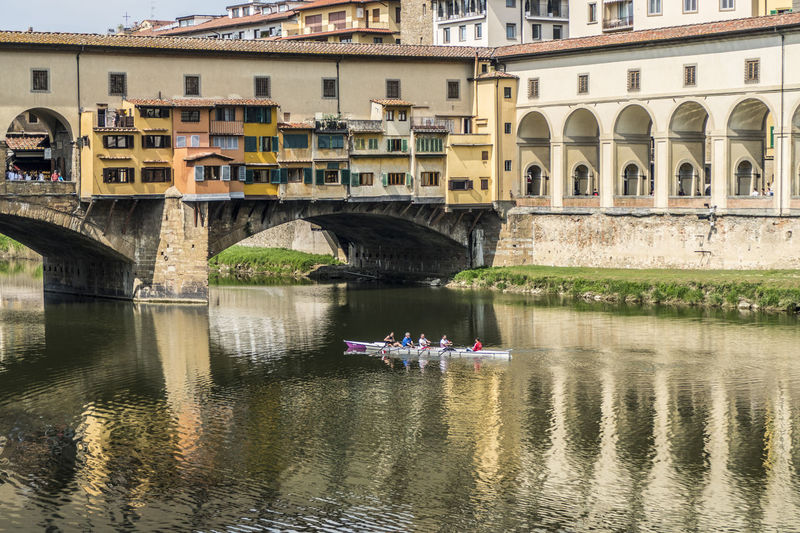 Bridge over river by buildings in city