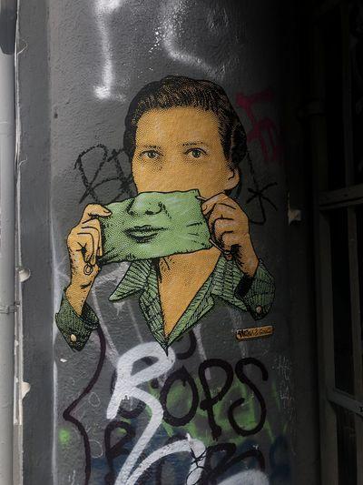 Close-up portrait of boy against graffiti wall