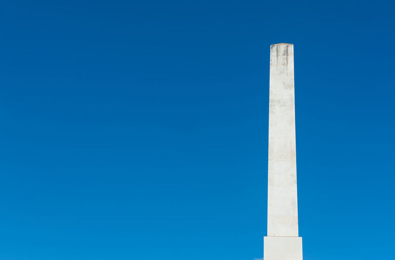 Low angle view of obelisk against clear blue sky