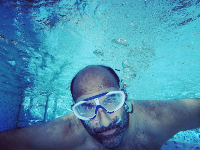 High angle portrait of man swimming in pool