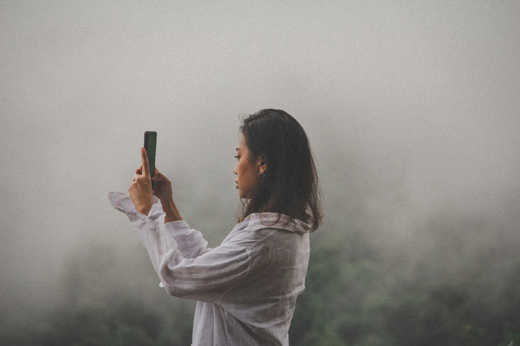Side view of young woman photographing from mobile phone during foggy weather