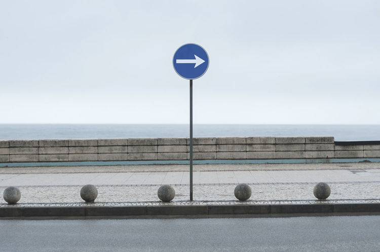 road sign at the atlantic Asphalt Atlantic Ocean Cloudy Gray Sky Portugal Sidewalk Sign Traffic Transportation Travel Arrow Symbol Blue Car Cobblestone Day Furadouro Horizon Over Water No People Outdoors Road Sign Sea Sky Street Symbol Turn Right