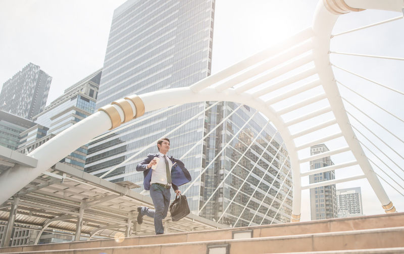 Low Angle View Of Businessman Moving On Steps Against Buildings In City