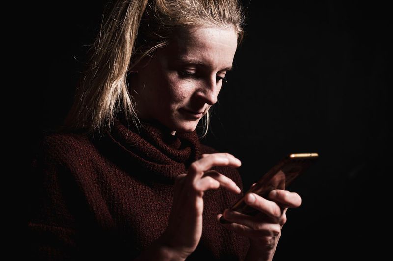 Close-up of woman using smartphone in darkroom