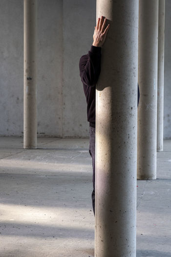 Midsection of woman standing on pole against wall
