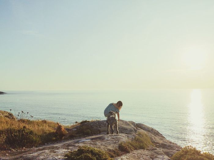 Woman with dog on rock by sea against sky