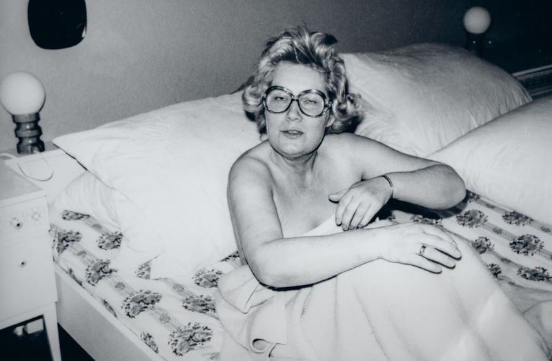 Portrait of shirtless man lying down on bed