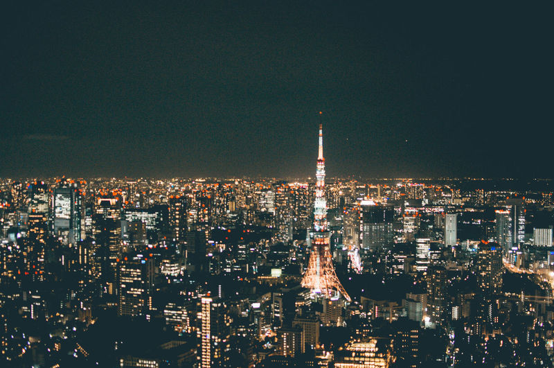 Illuminated tokyo tower amidst cityscape at night