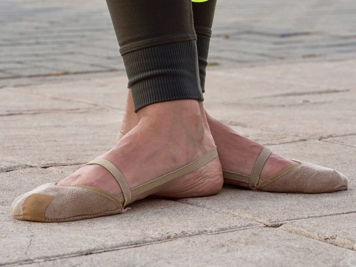 Low Section Of Woman In Ballet Shoes Standing On Paving Street