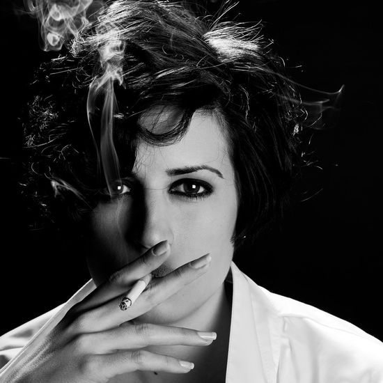 Close-Up Portrait Of Young Woman Smoking Cigarette Against Black Background