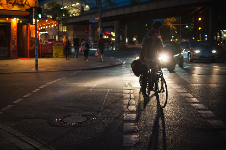 People riding bicycle on road at night