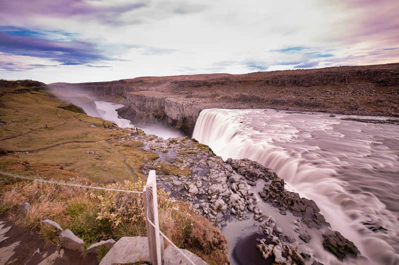 Scenic view of flowing water against sky