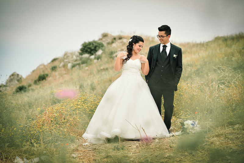 Newlywed Couple Standing On Grassy Field Against Sky