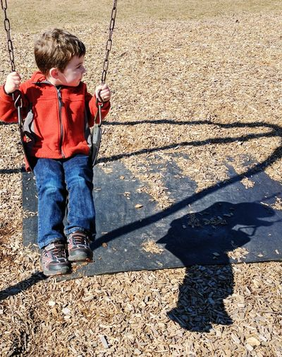 High angle view of boy enjoying on swing at park