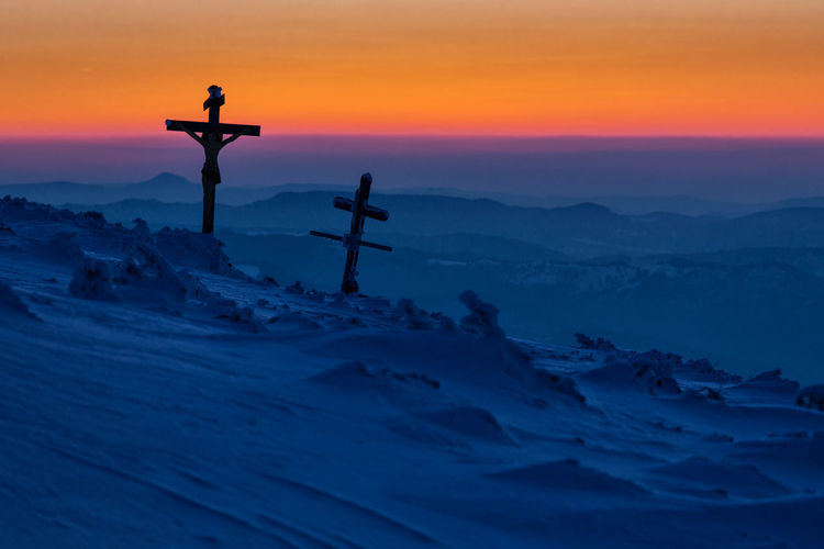 Silhouette crosses on snow covered mountain against sky during sunset