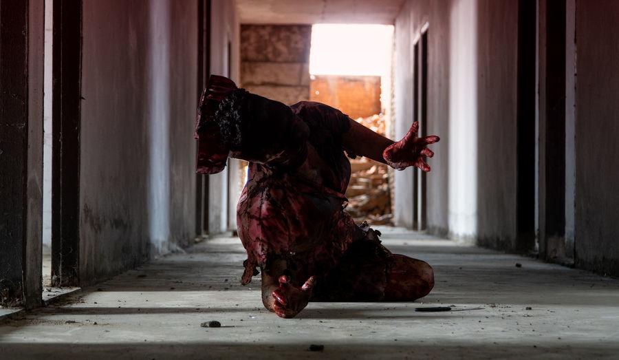 Man wearing spooky halloween costume lying on floor