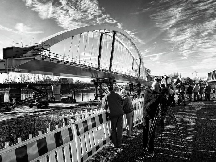 People standing by incomplete arch bridge against sky