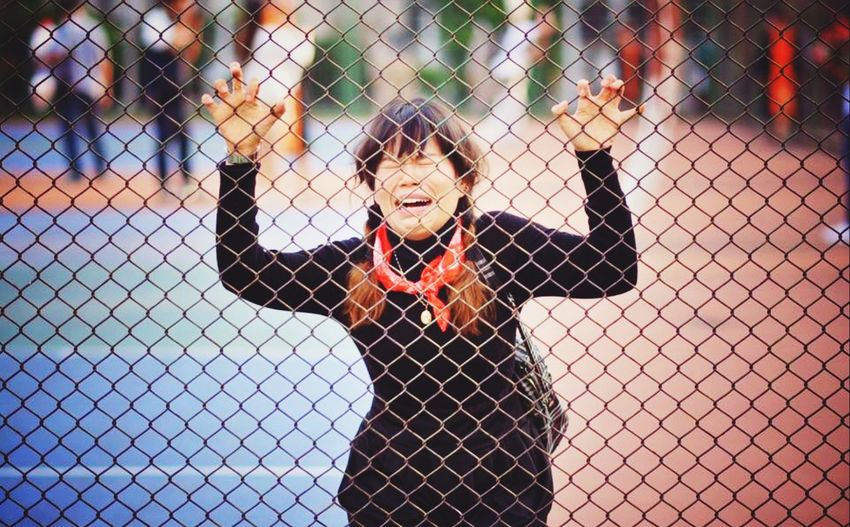 Woman crying while standing by chainlink fence