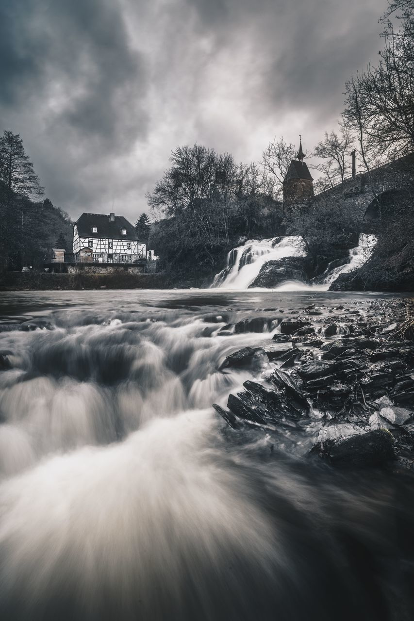 water, sky, nature, cloud - sky, motion, no people, waterfall, tree, outdoors, architecture, scenics, beauty in nature, built structure, long exposure, tranquility, day, sea, mountain, building exterior