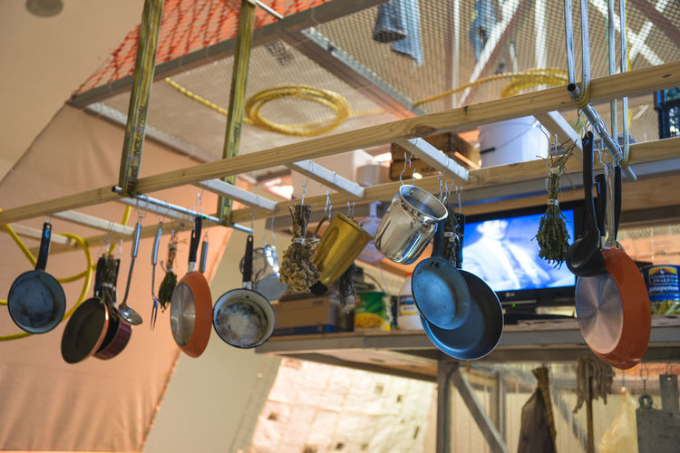 Low angle view of cooking utensils hanging from rack
