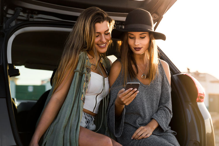 Female friends using phone while sitting in car trunk during sunset
