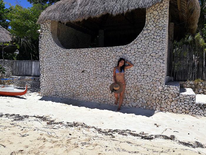 Woman in bikini standing against wall