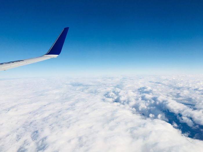 Cropped image of aircraft wing in mid-air against sky