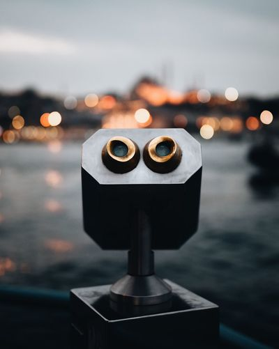 Close-Up Of Coin-Operated Binoculars Against Sea At Dusk