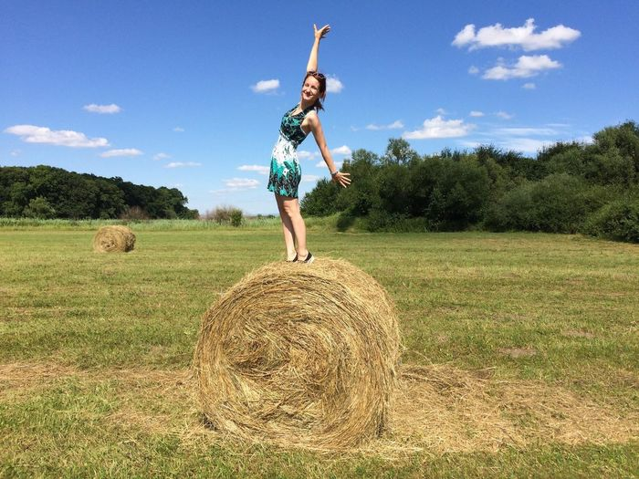 Cheerful Woman Balancing On Hay Bale At Farm Against Sky