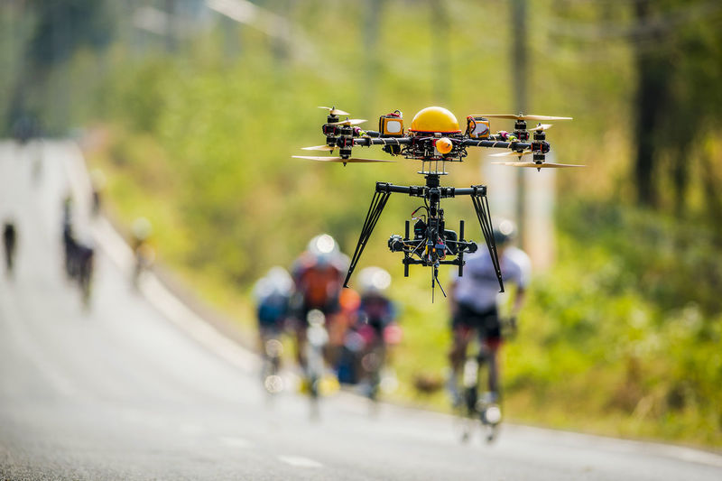 Drone flying in the sky Activity Bicycle City Day Flying Flying In The Sky Focus On Foreground Full Length Group Of People Helmet Land Vehicle Men Mode Of Transportation Motion Outdoors People Real People Riding Road Selective Focus Sport Technology Transportation