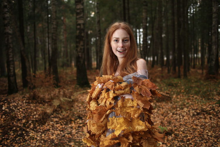 Portrait of smiling young woman covered with leaves standing at forest during autumn