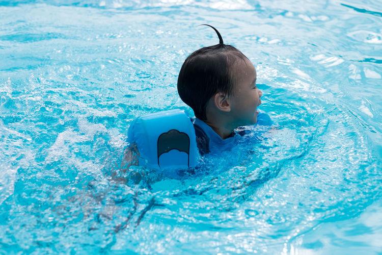 Boy Wearing Water Wings While Swimming In Pool
