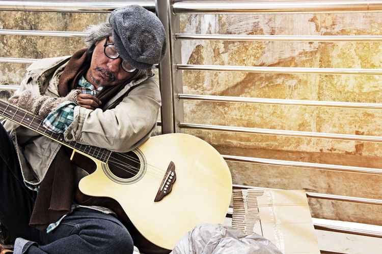 Homeless Man Sitting With Guitar Against Railing