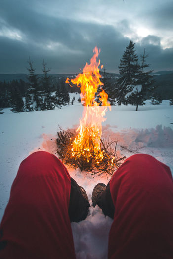 Low section of man sitting on snow by bonfire