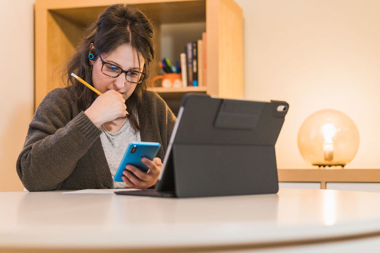 Portrait of woman using mobile phone at home