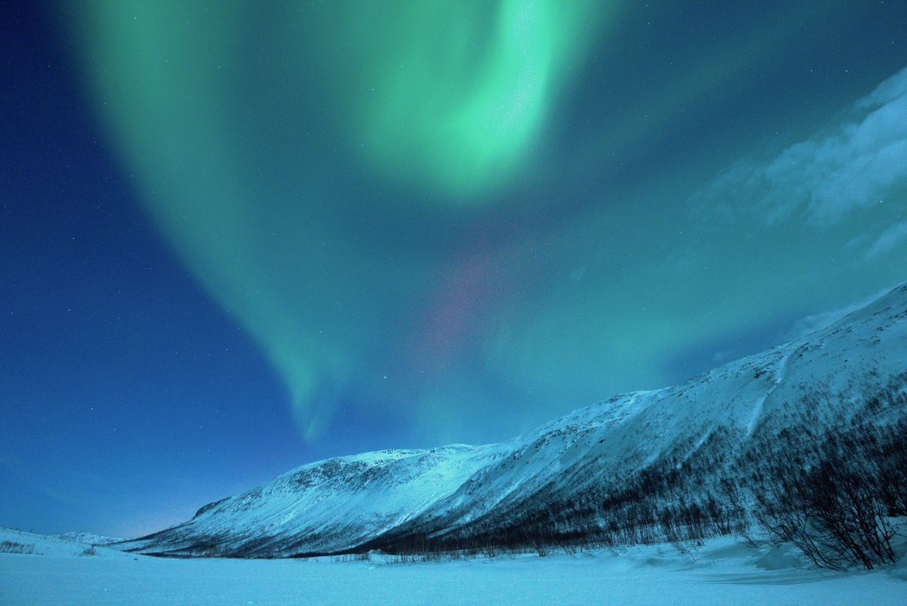 Idyllic view of northern lights over snowcapped landscape at dusk